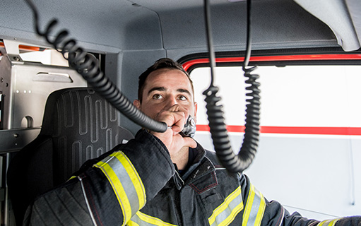 fireman in firetruck talking on radio